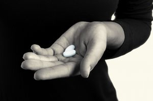 Black and white toned photo, open palm with blue pills, links to overdose prevention page